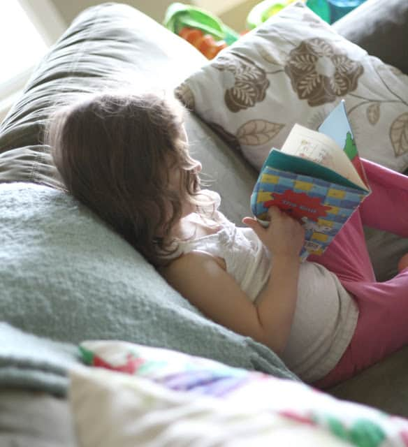 preschooler reading on a couch
