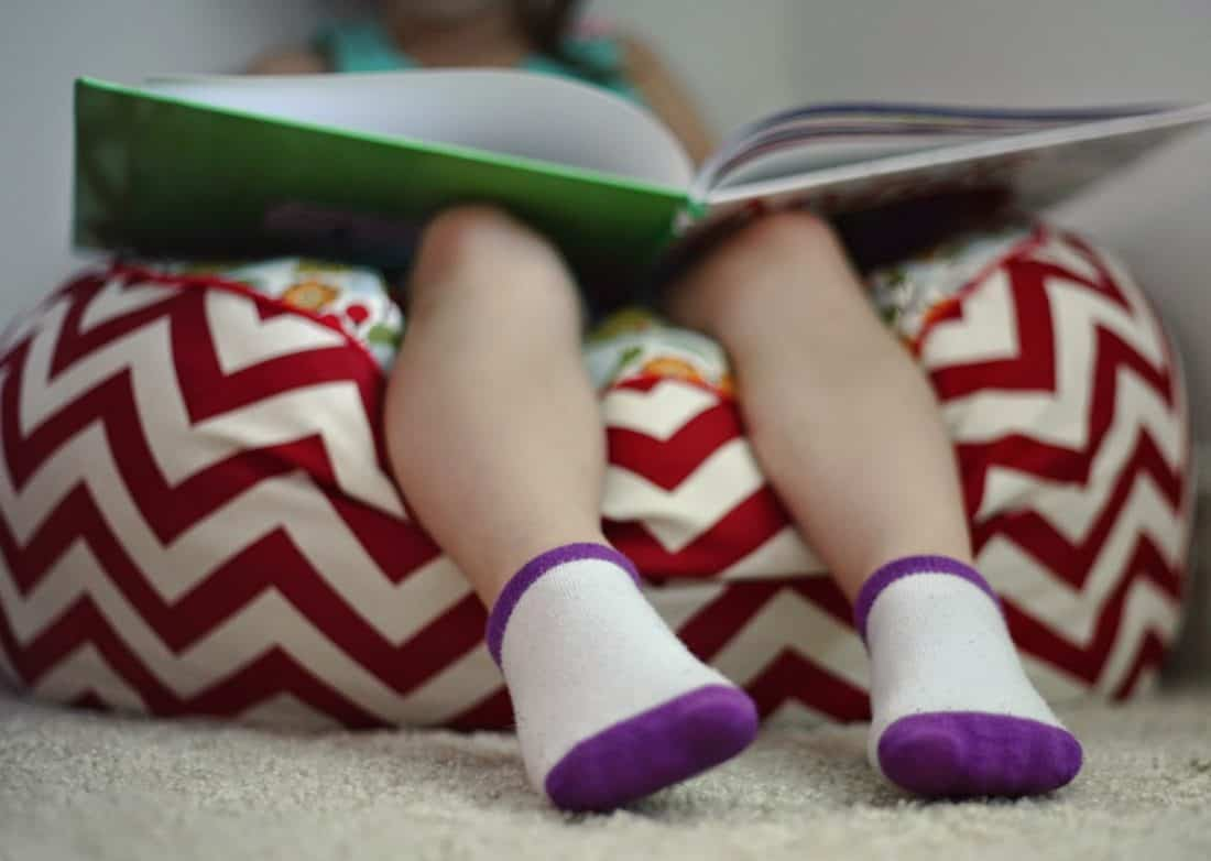 toddler sitting on floor pouf reading a book