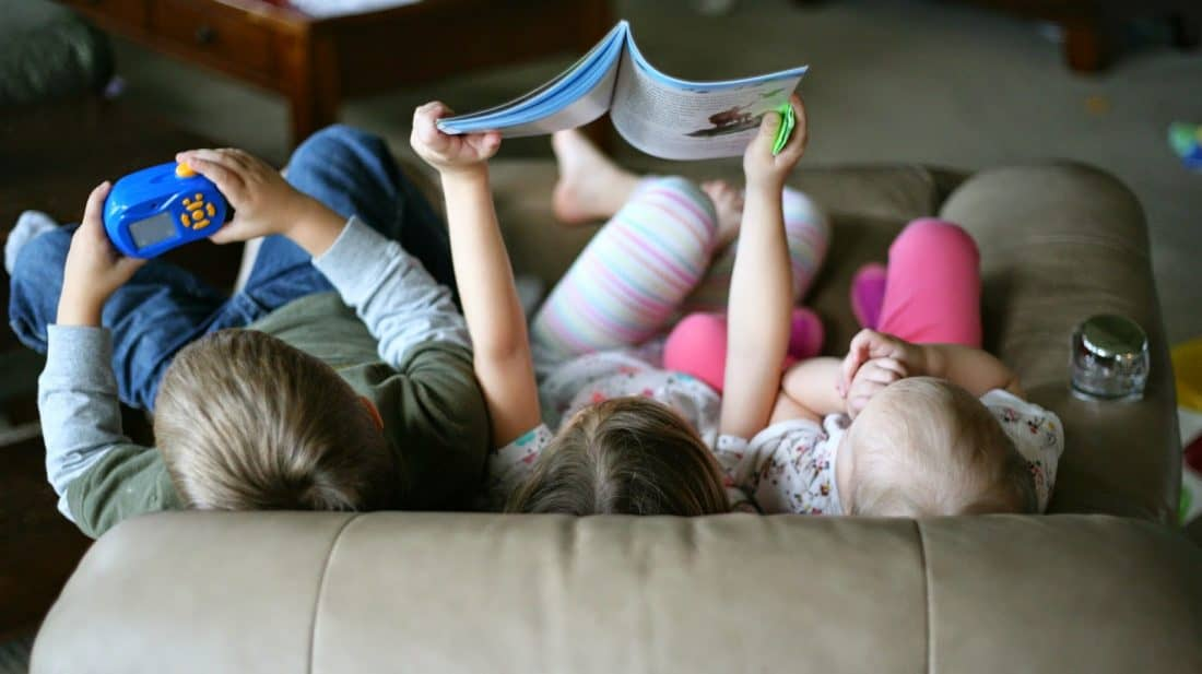 kids sitting on the couch reading together