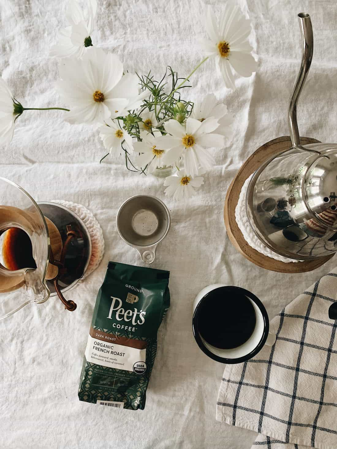 peet's organic coffee sitting on a table with a white linen tablecloth covering it.  a tea kettle and chemex pour over is sitting on the table also.