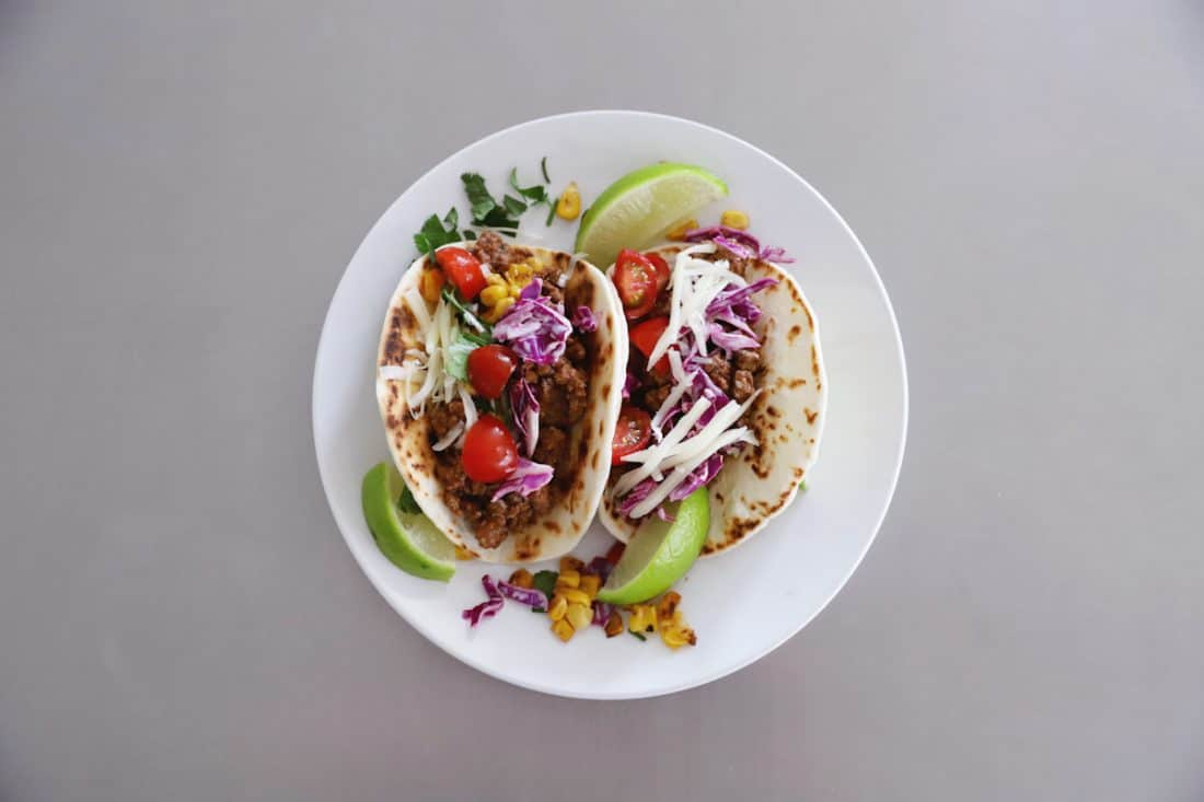 two street tacos filled with delicious taco side dishes on a white plate