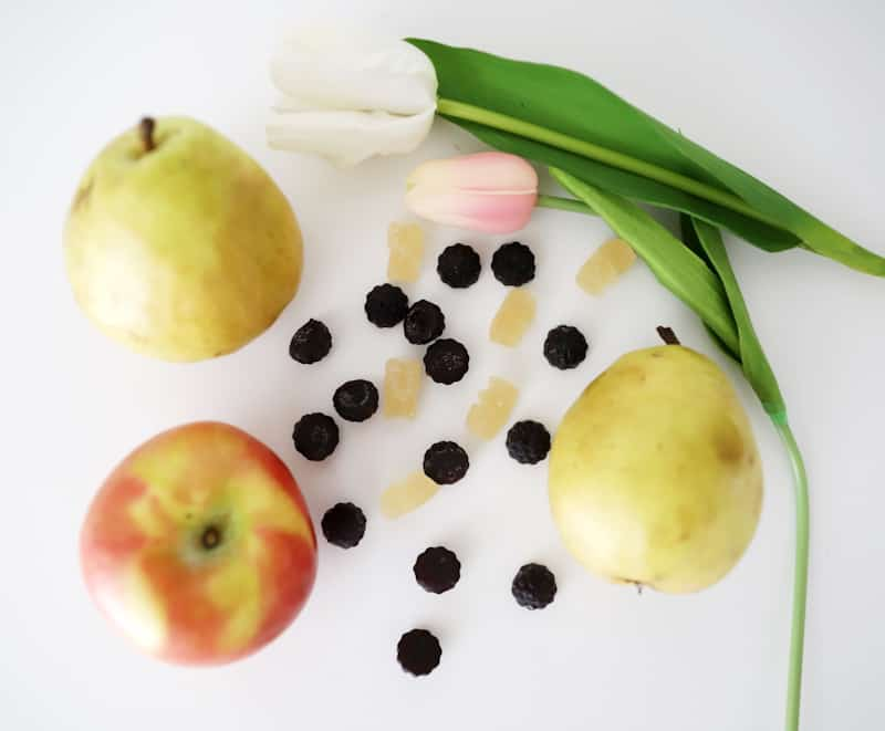 two pears, an apple, and two tulips on a white counter with organic vitamin gummies scattered on the counter