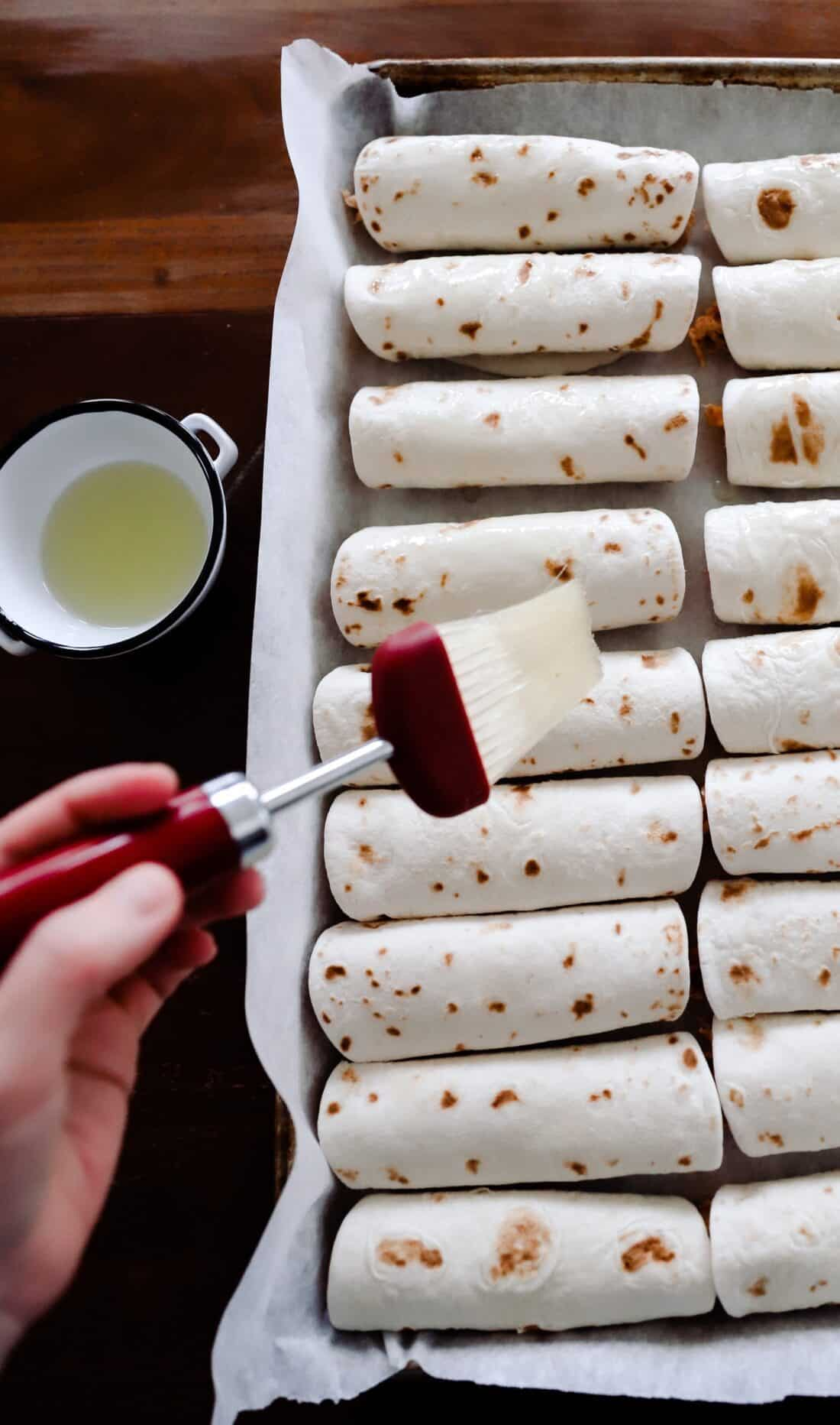 unbaked tortillas being brushed with oil and salted