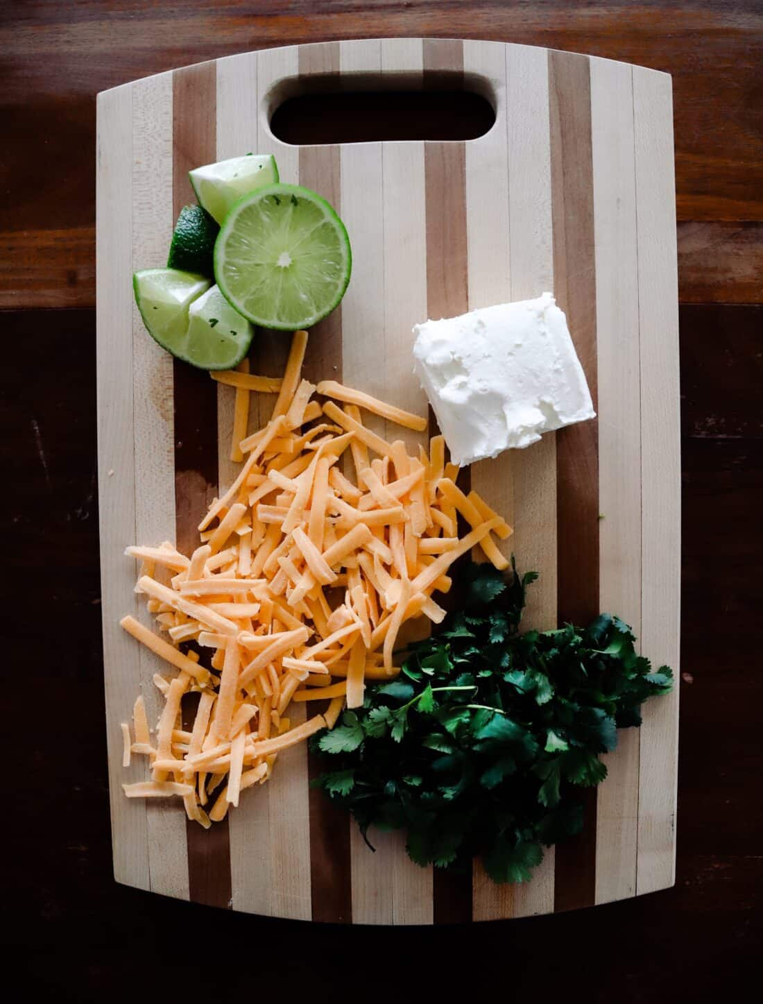 lime, cilantro, cream cheese, and shredded cheese on wooden cutting board