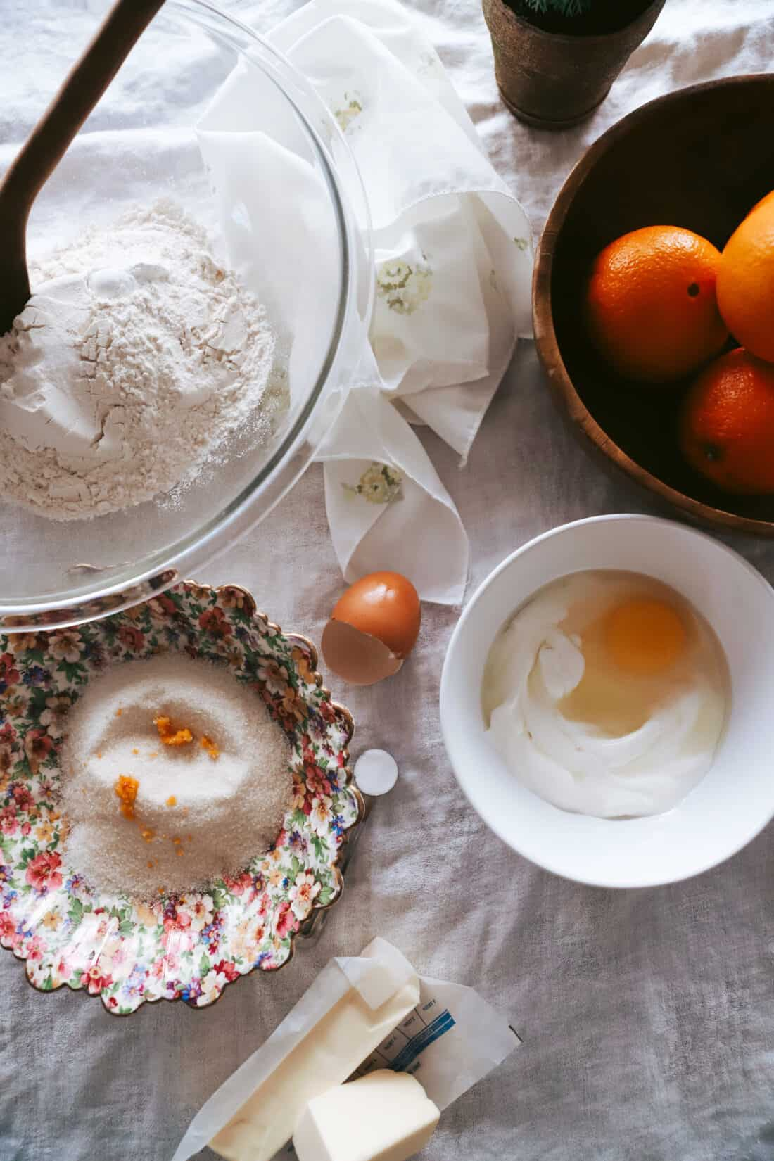 ingredients for orange scones in bowls on a table with a white table cloth