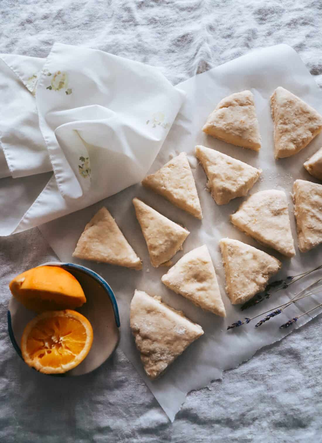orange scone dough cut into wedges and laying on parchment paper on a table