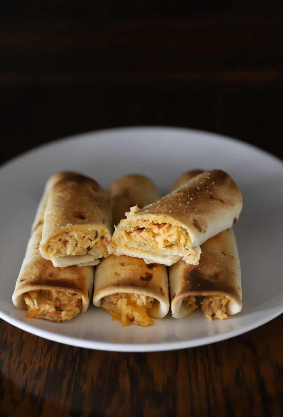 baked hot chicken taquitos on a white plate and wooden table