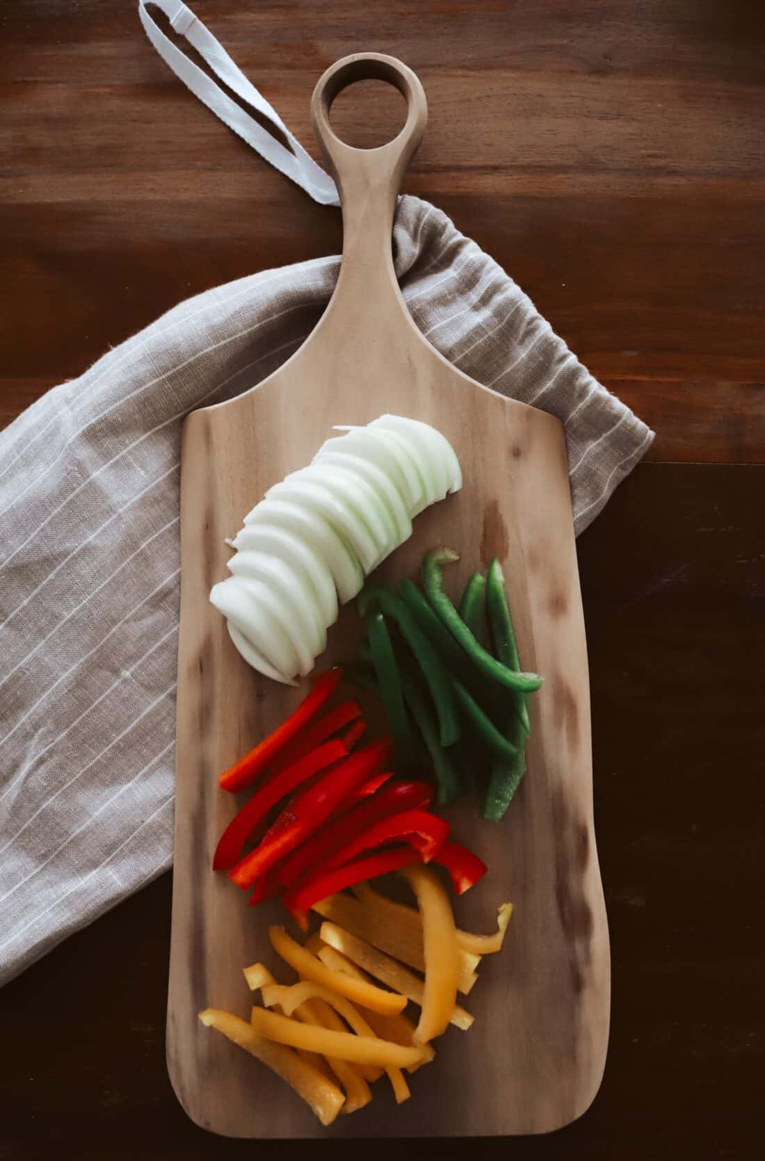 sliced peppers and onion on a wooden cutting board