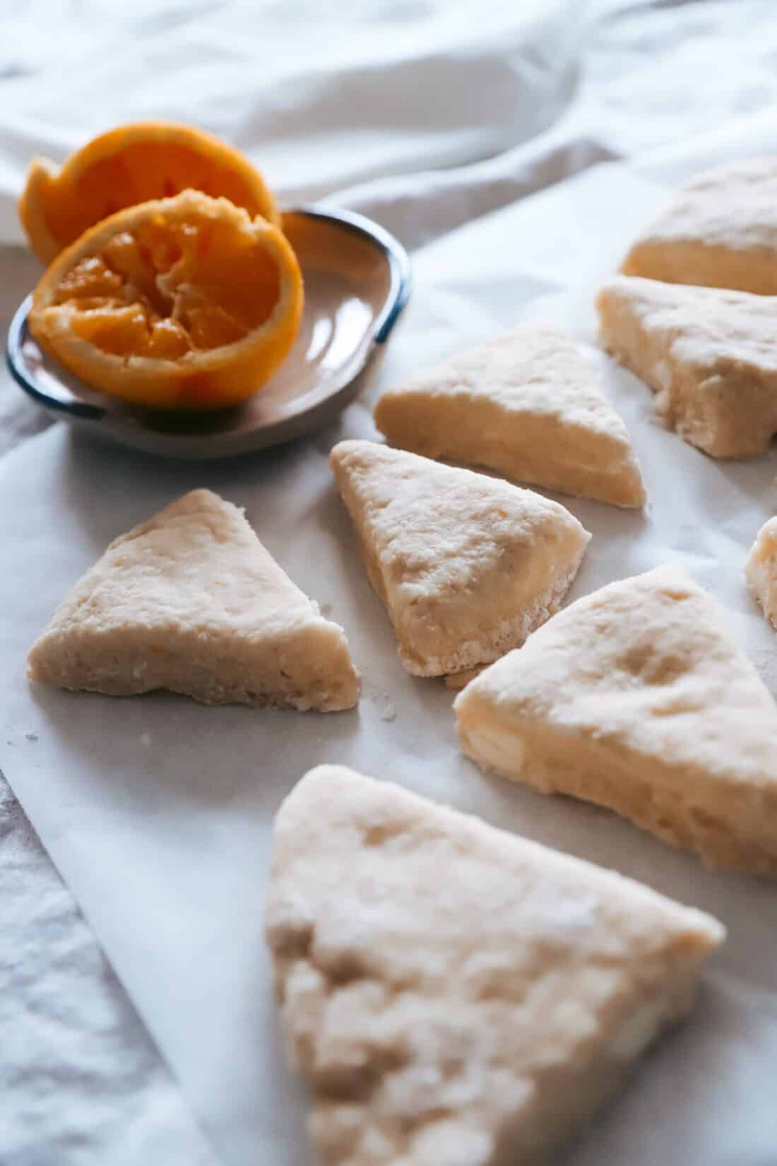 orange scone dough wedged laying on the table ready to be baked