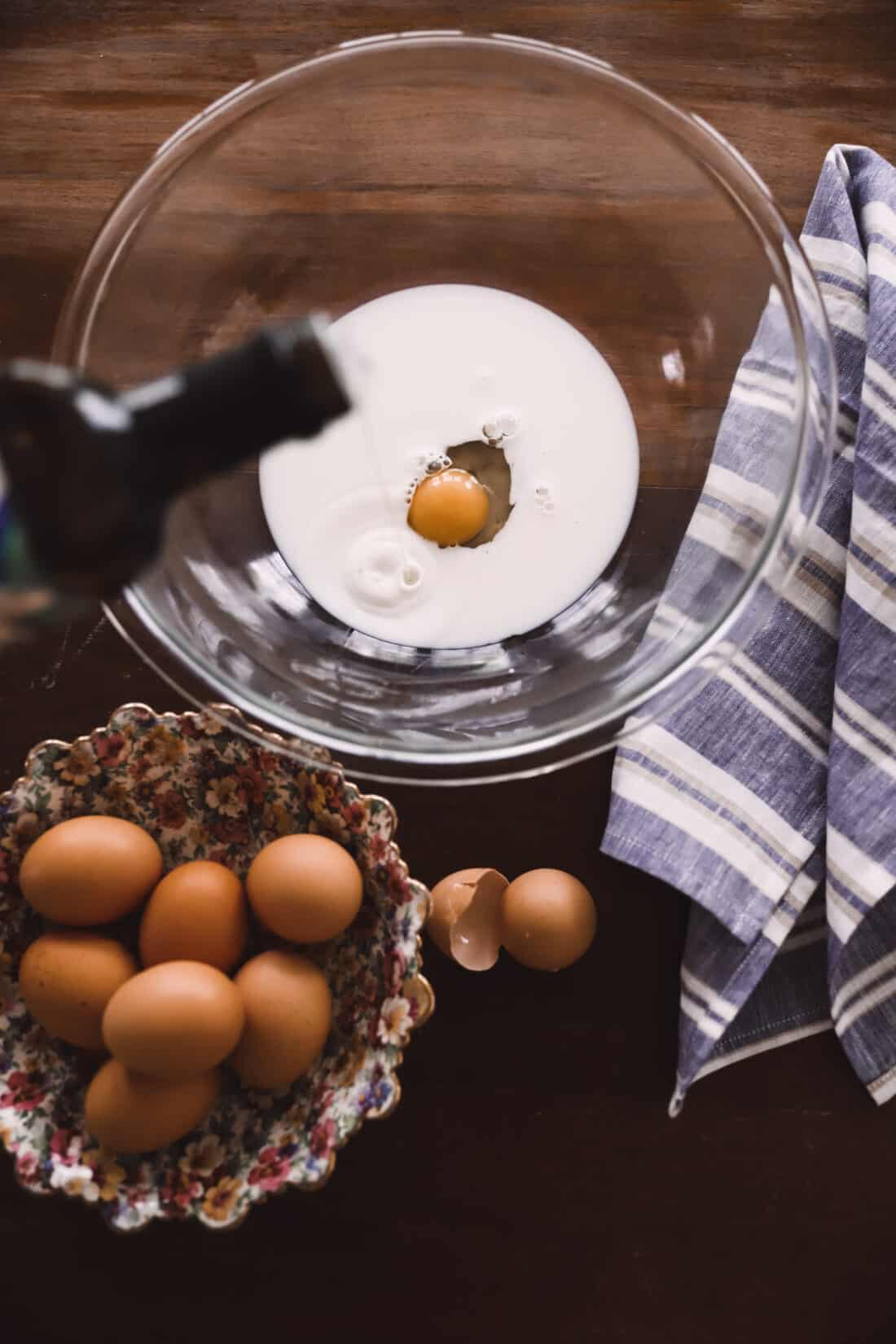pancake ingredients on a wooden table with a floral china bowl holding eggs