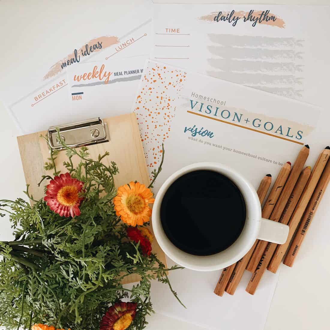 homeschool printables laying on a white counter with coffee, colored pencils, and flowers on top