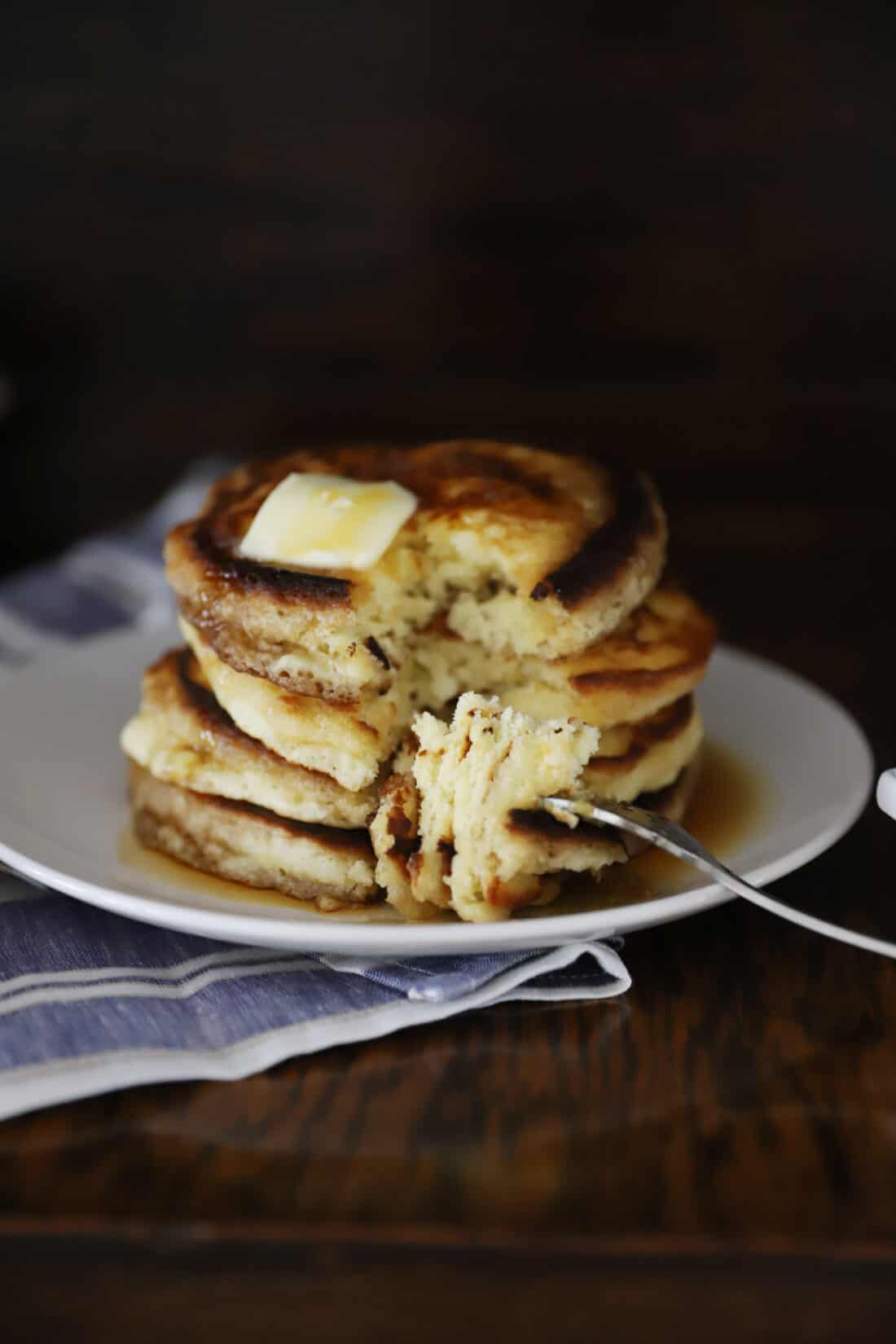 a stack of pancakes without buttermilk in them with a huge bite on a fork, ready to be eaten