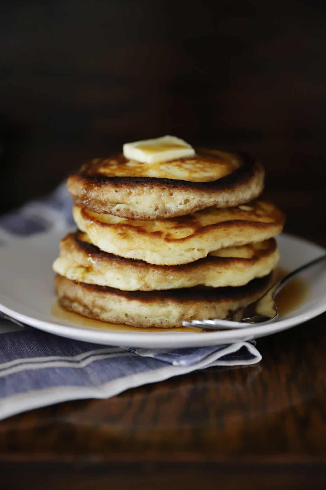 a stack of hot pancakes with butter on top and syrup