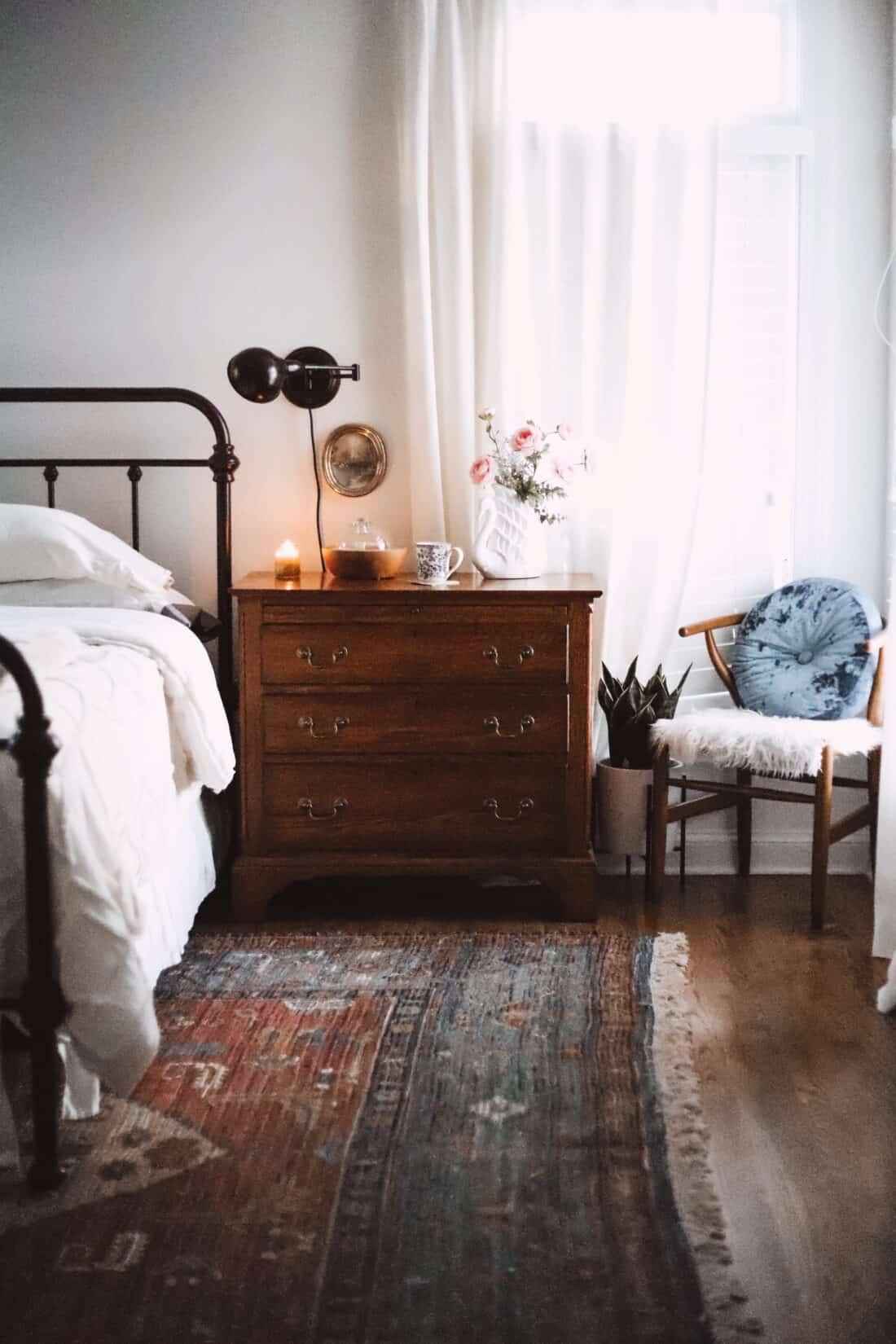 beeswax jar candle burning on a bedroom nightstand