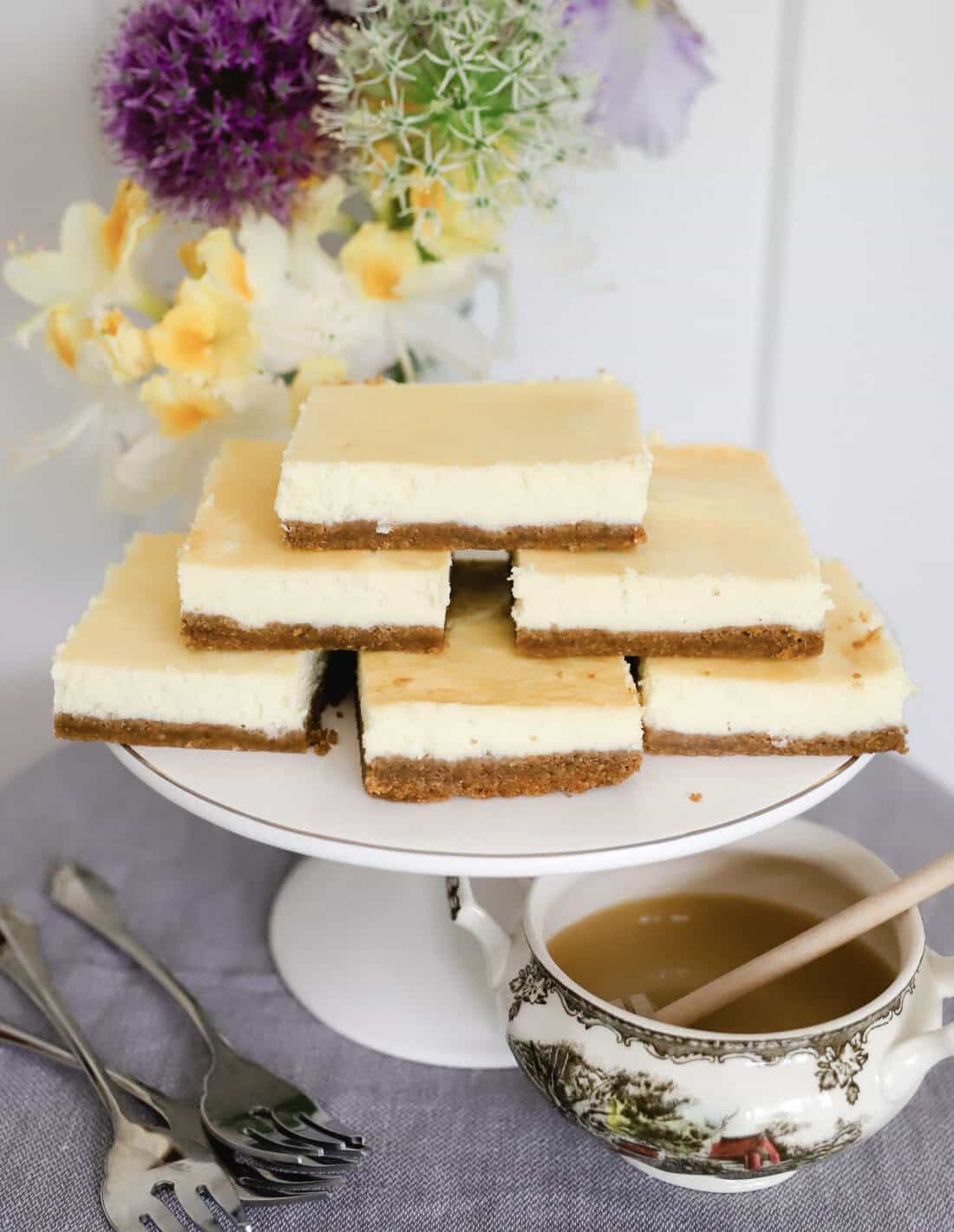 cheesecake cut into squares on a white platter