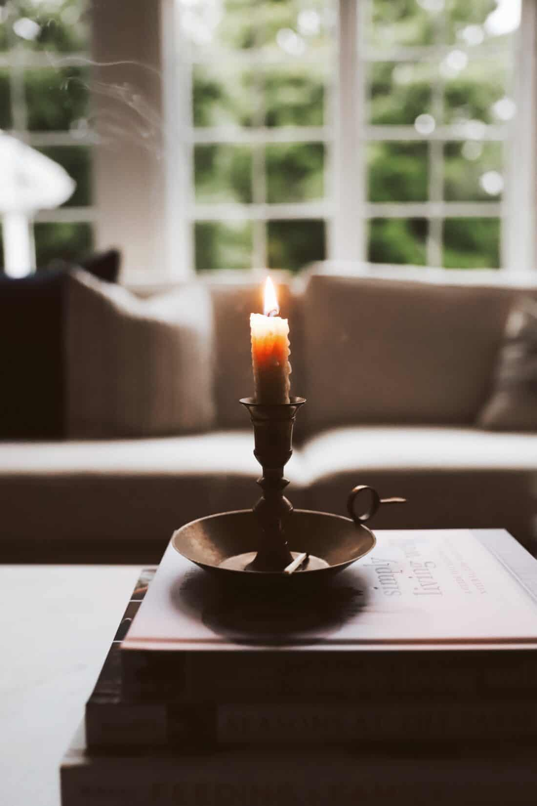 rolled taper candle in a brass holder on a coffee table