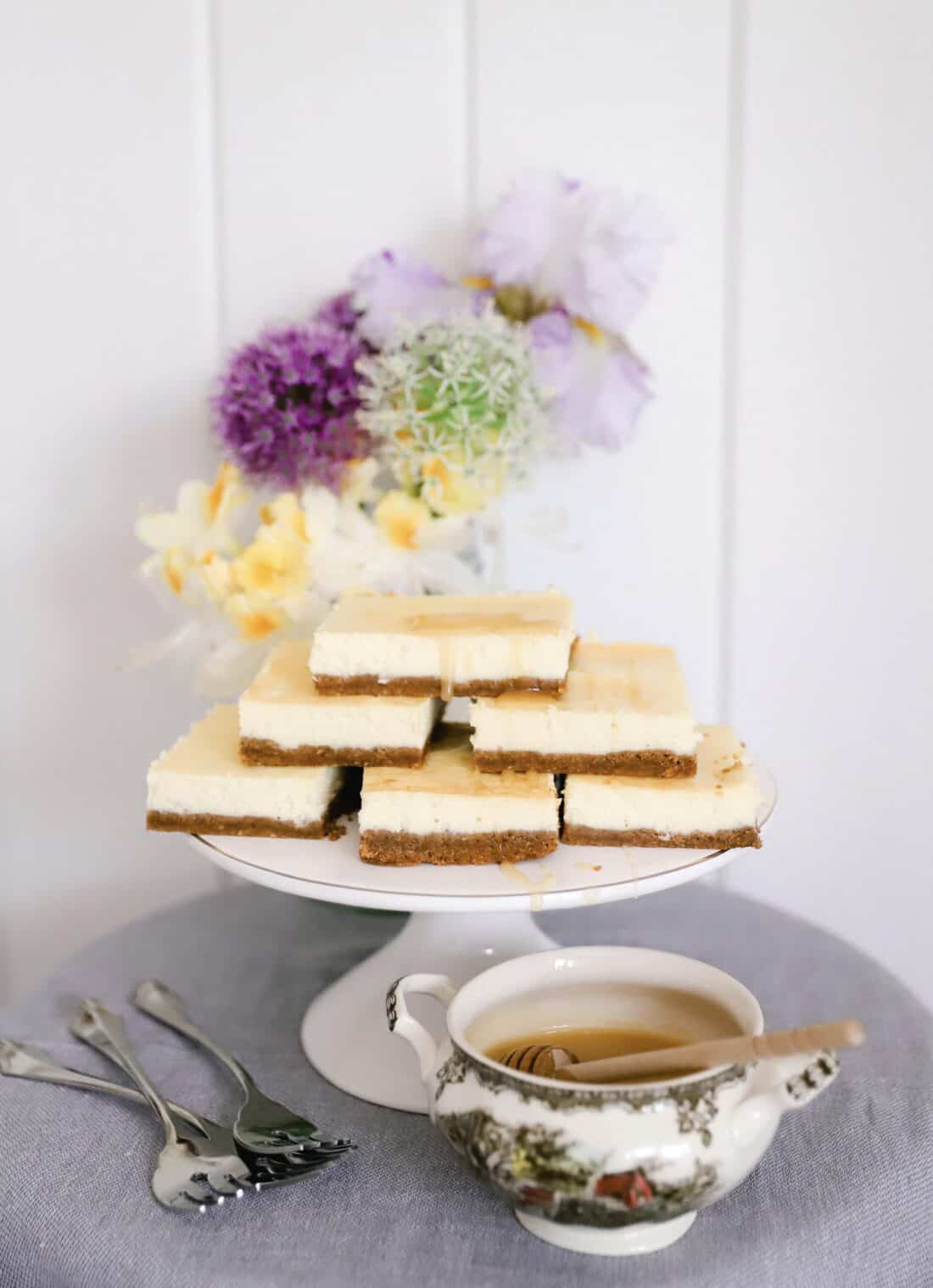 six pieces of cheesecake with spring flowers in the background