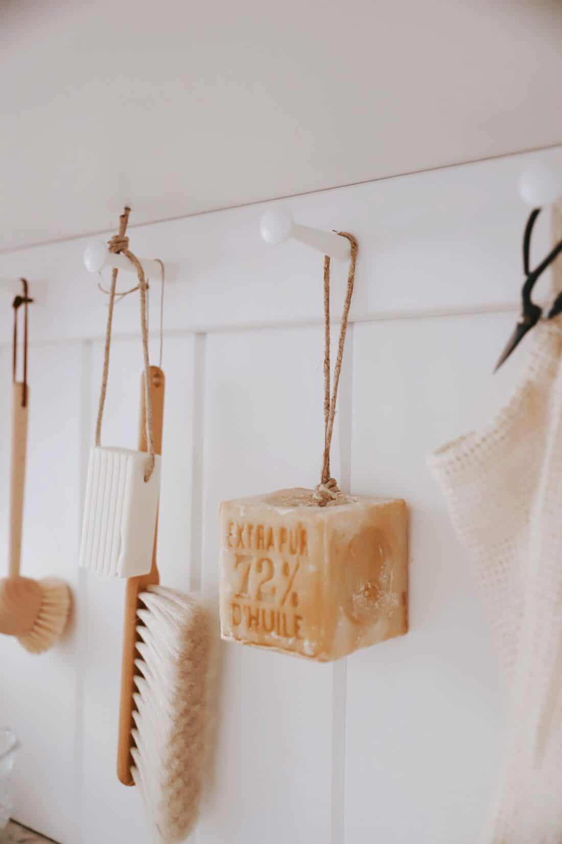 wooden peg rack in a kitchen with french soap on a rope and wooden brushes hanging from it