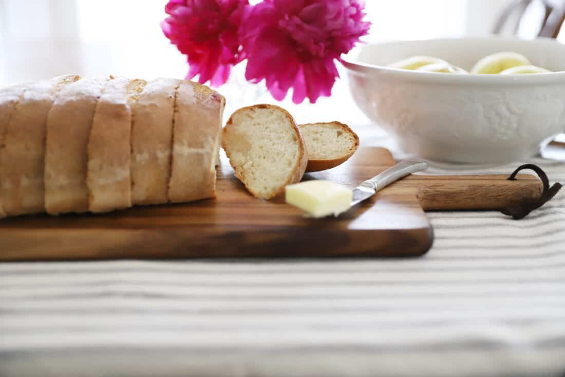 sliced sourdough french loaf with a pat of butter