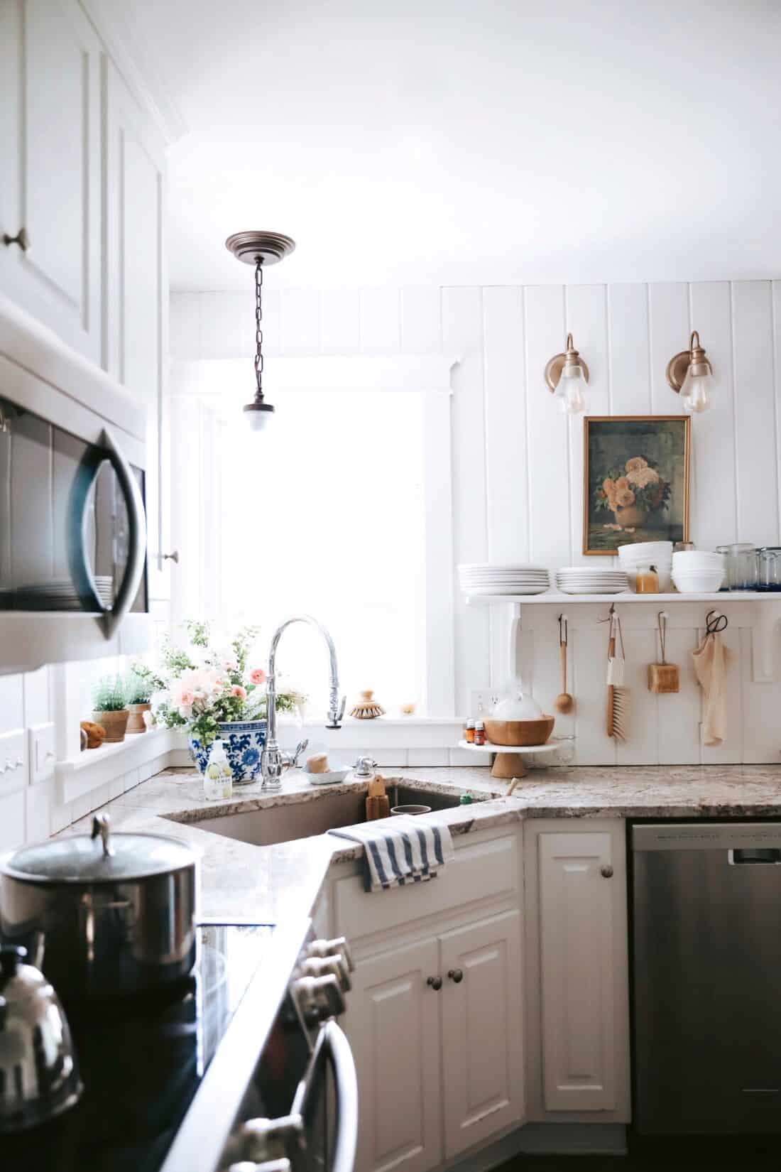 a kitchen with white, vertical shiplap boards and open shelving with a wooden peg rack