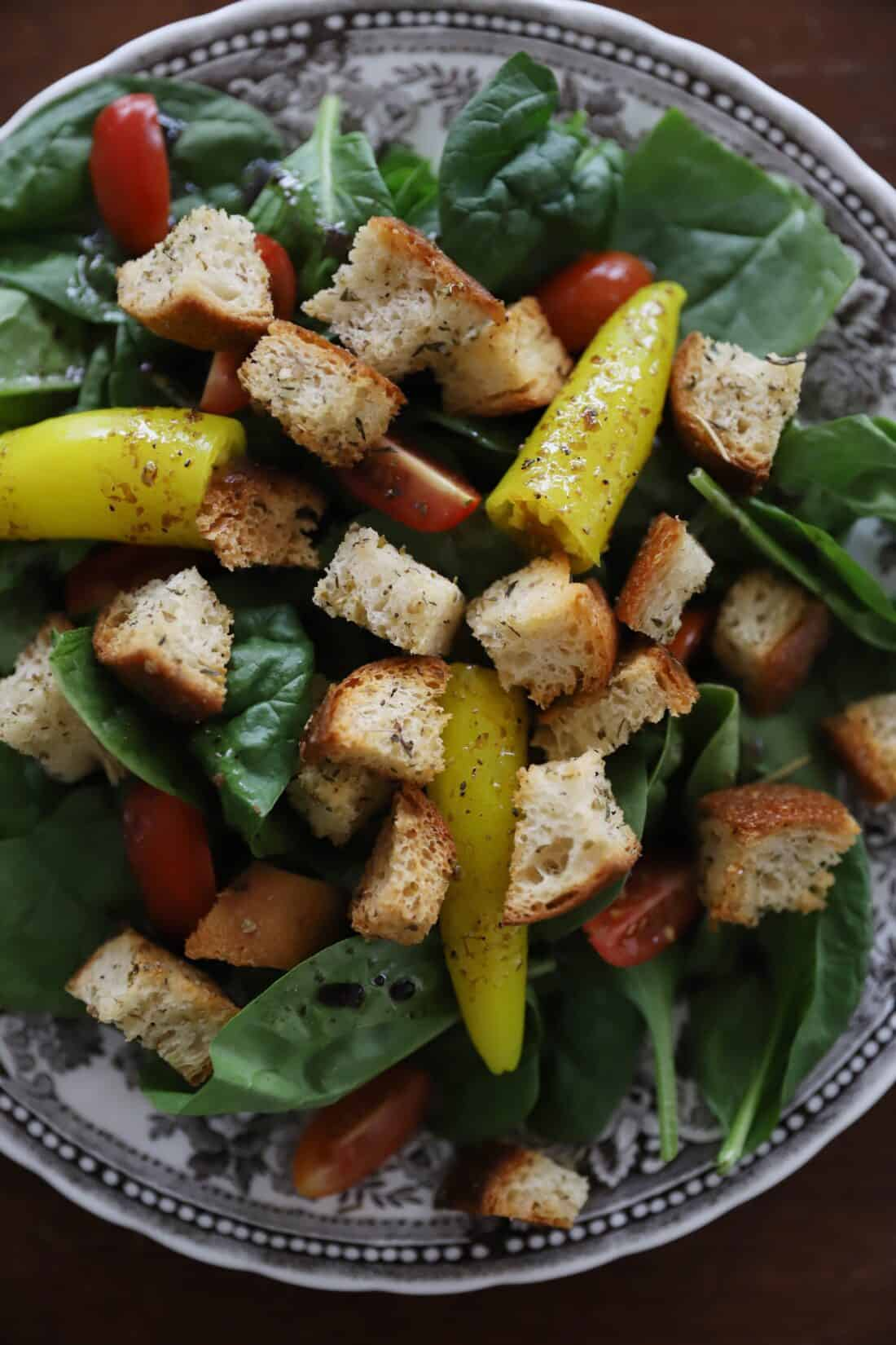 easy sourdough italian croutons from scratch on a plate with tomatoes