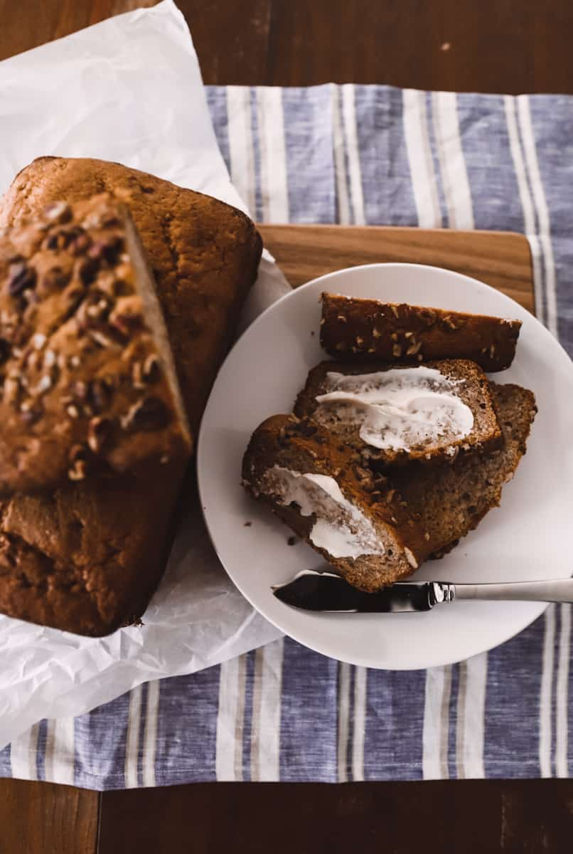 greek yogurt banana bread with nuts on a cutting board with butter and a butter knife
