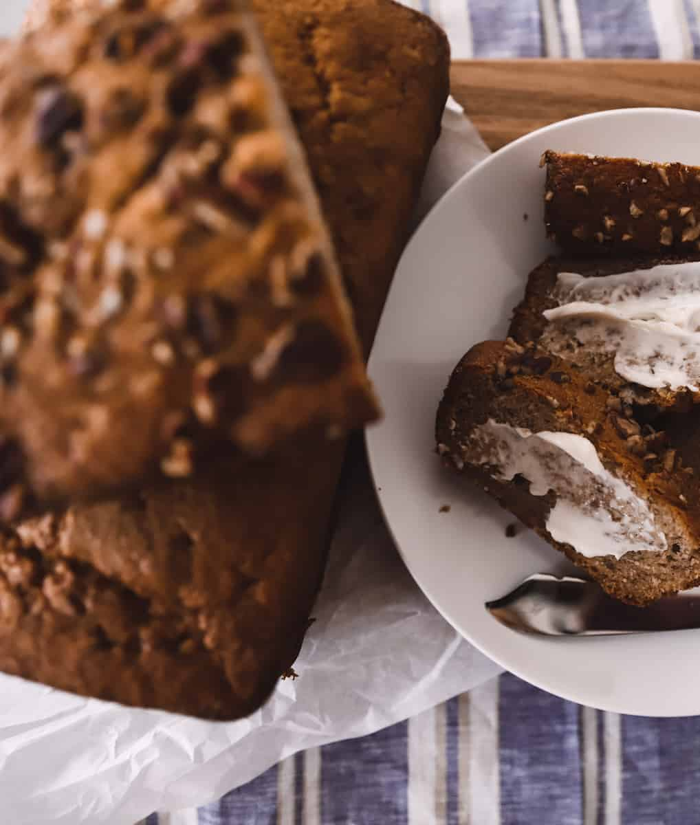 greek yogurt banana bread with nuts on a cutting board with butter