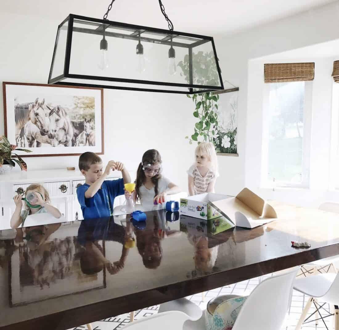four homeschool kids doing a science experiment and a preschooler
