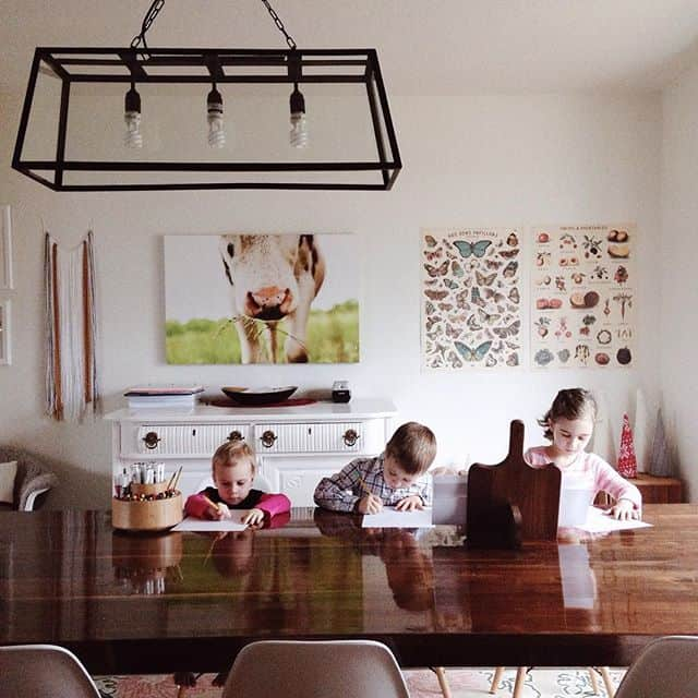 three homeschool kids working at a wooden table with a preschooler