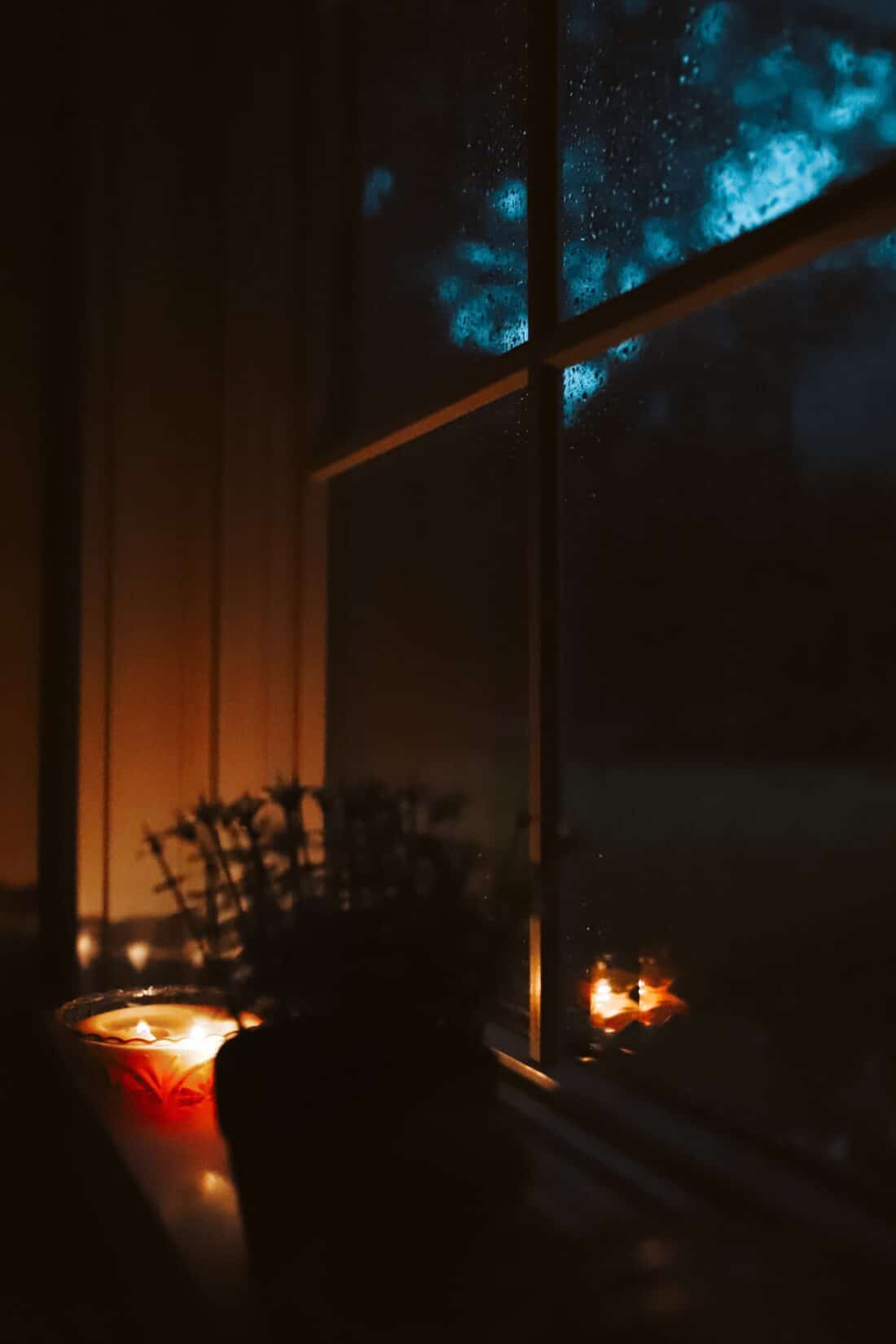 a stormy morning that is dark outside with a candle burning