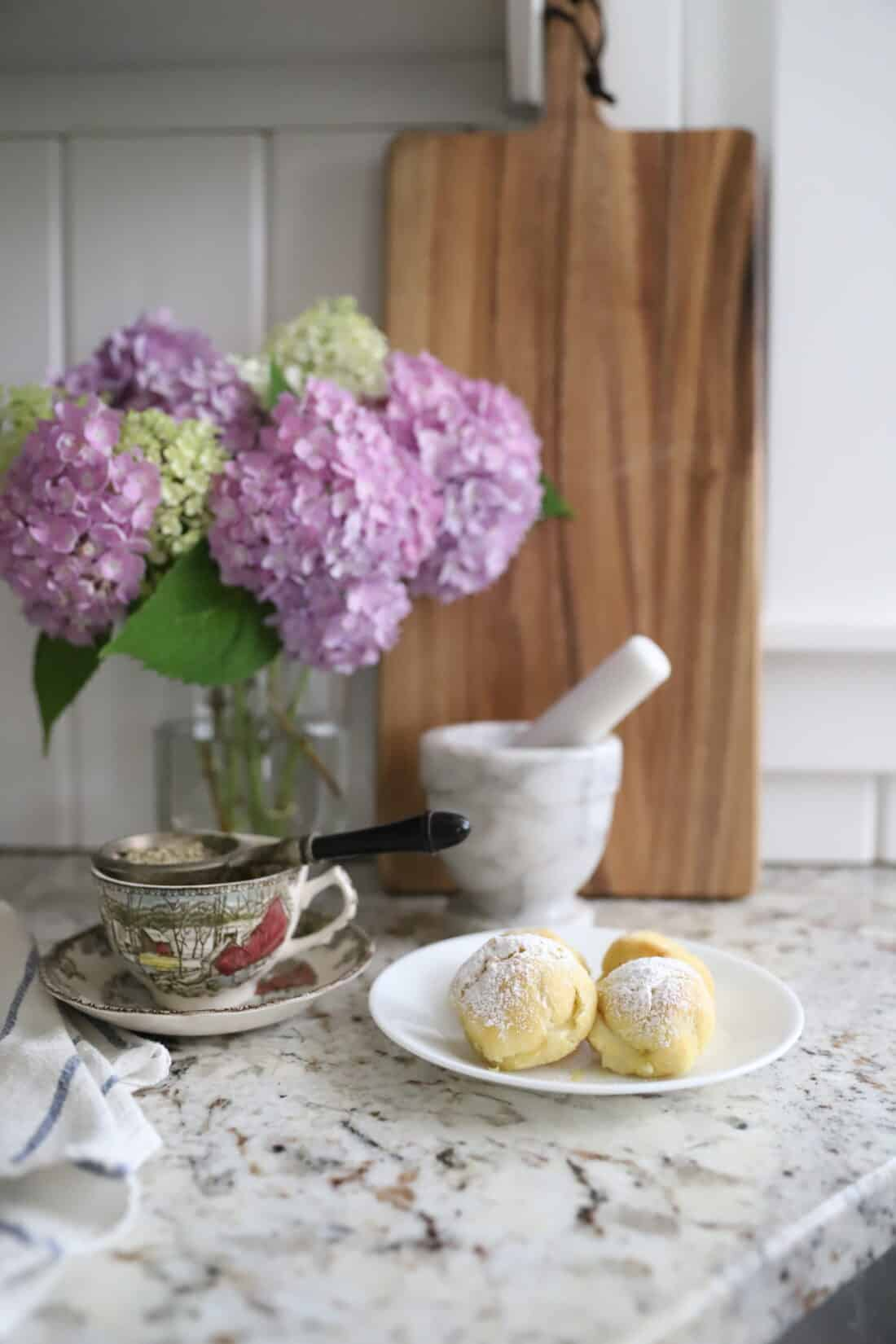 cream puffs and a cup of tea on a kitchen counter