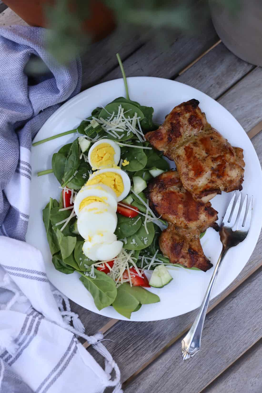 Grilled Smoked Chicken Thighs with a side salad on a wooden table