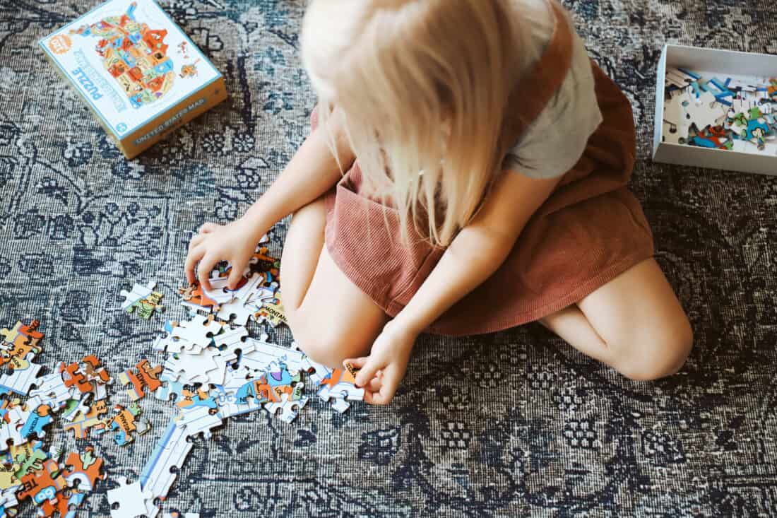 child doing a puzzle on the ground