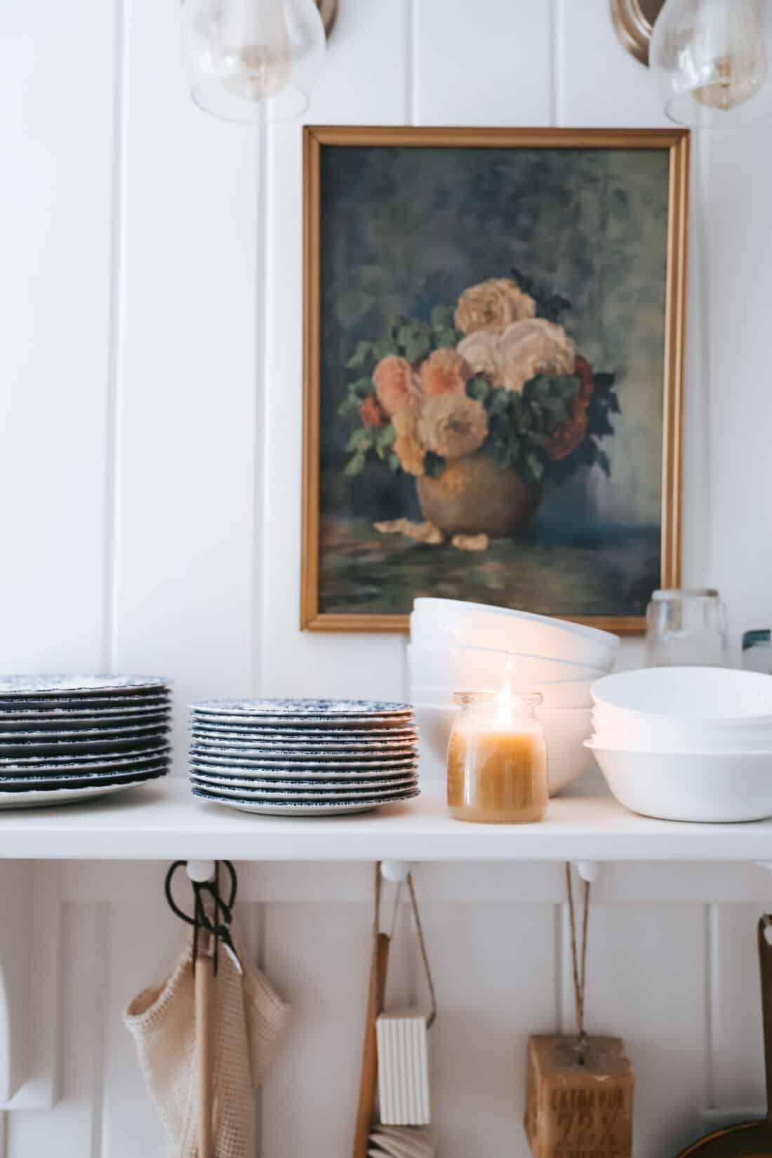 white vertical shiplap in a cottage kitchen with a beeswax candle and vintage art
