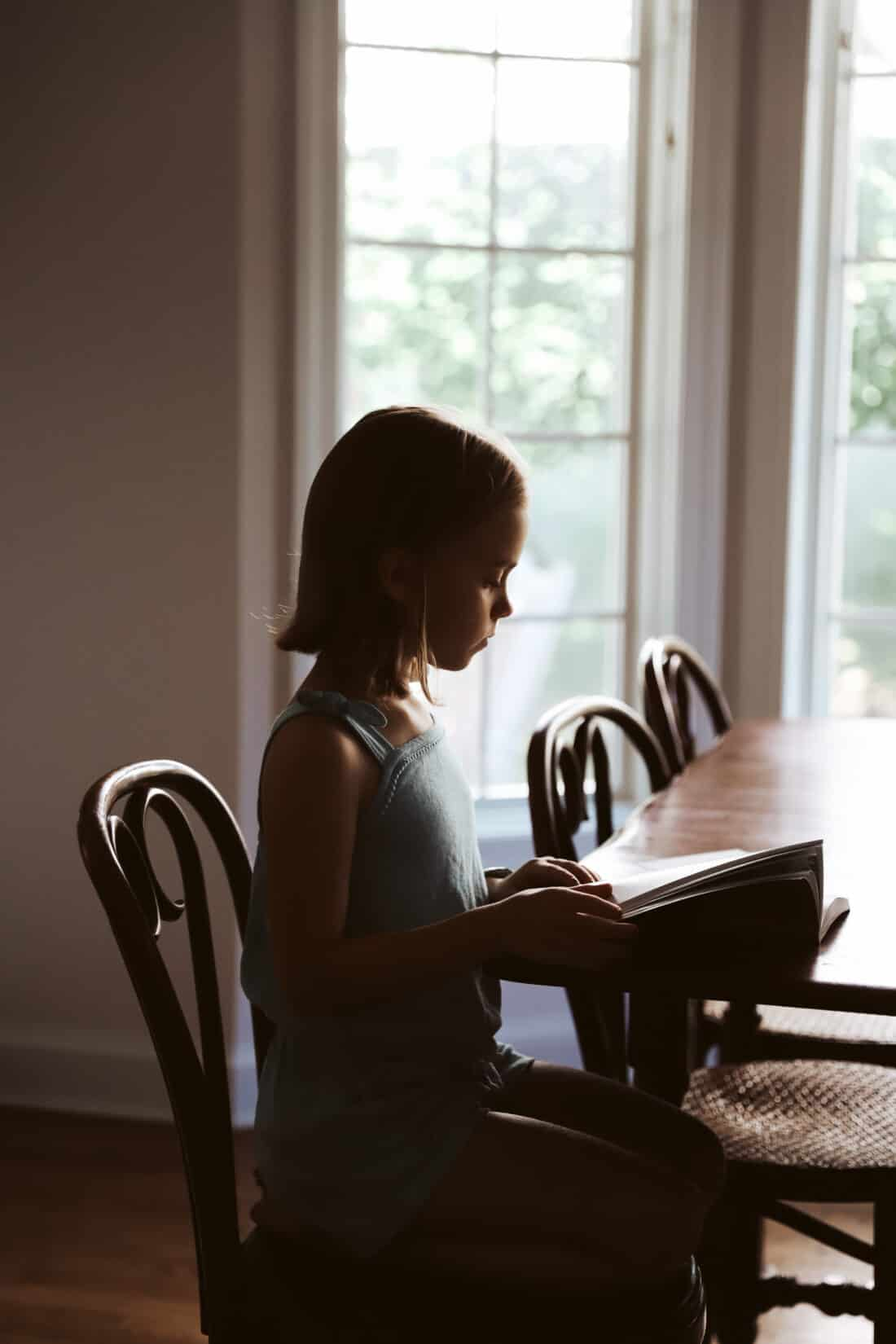 child reading a book at a table