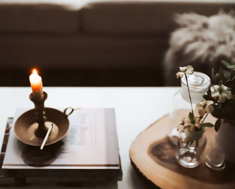 candle on top of book with a wooden match
