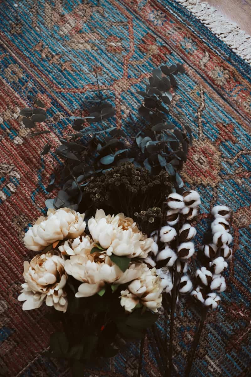 faux flowers on a vintage rug