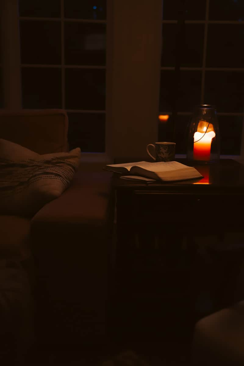 candle glowing on a table with a cup of coffee in the morning