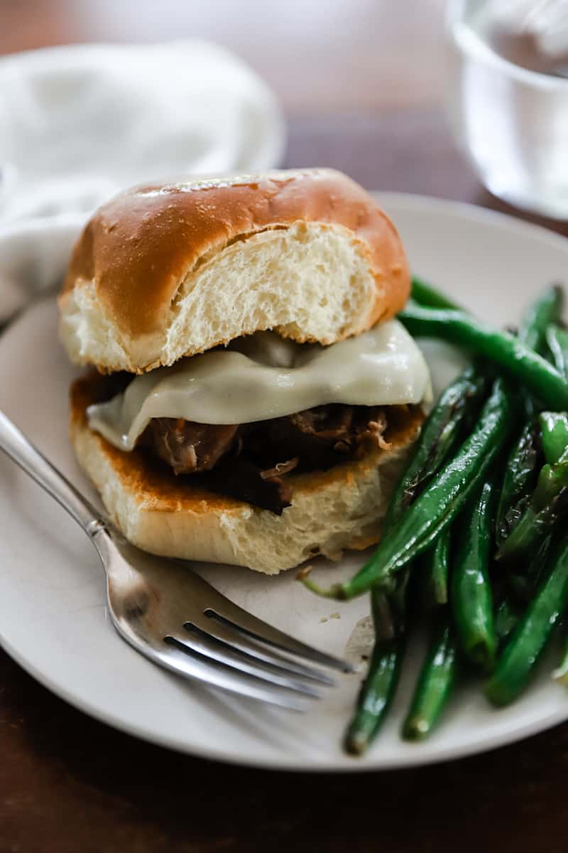 french dip sandwich with green beans on brioche bread