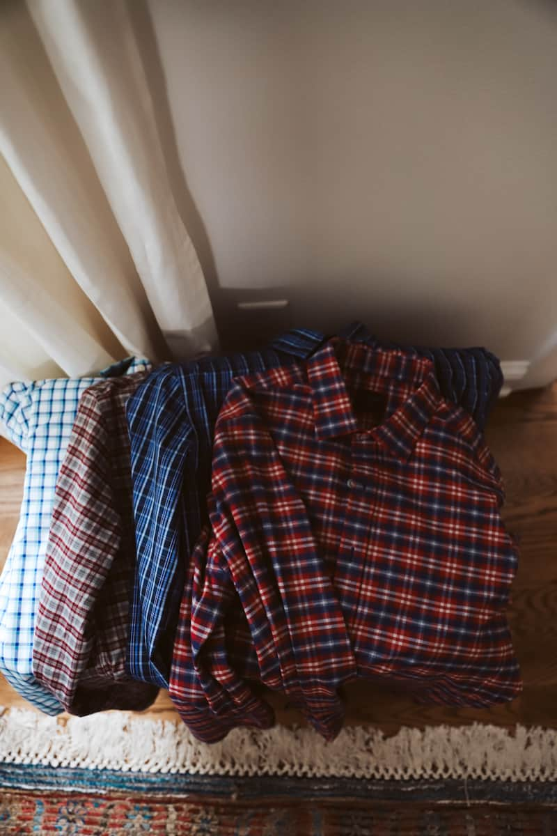 button down shirts laying on a basket