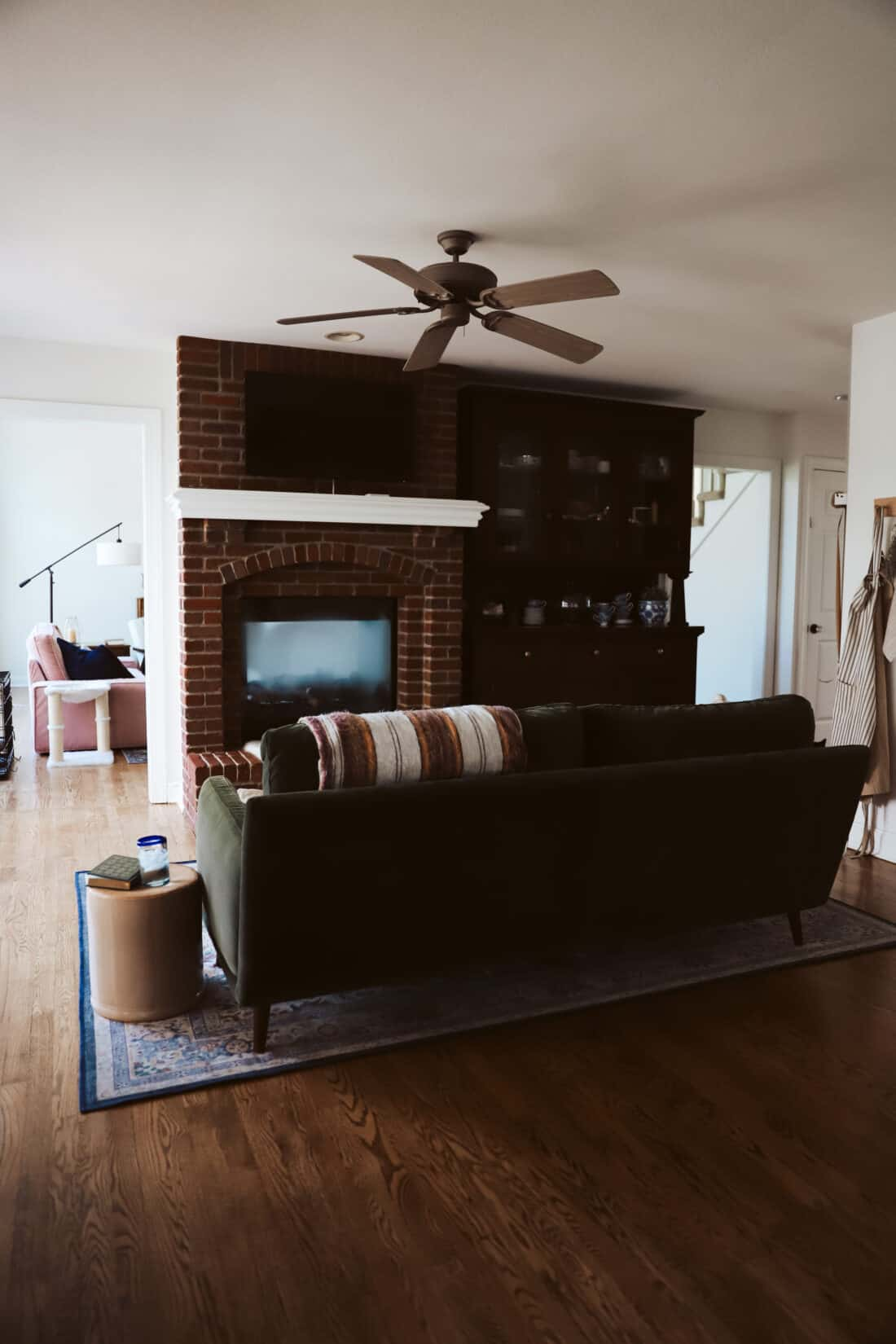 green velvet sofa in a keeping room with a red brick fireplace