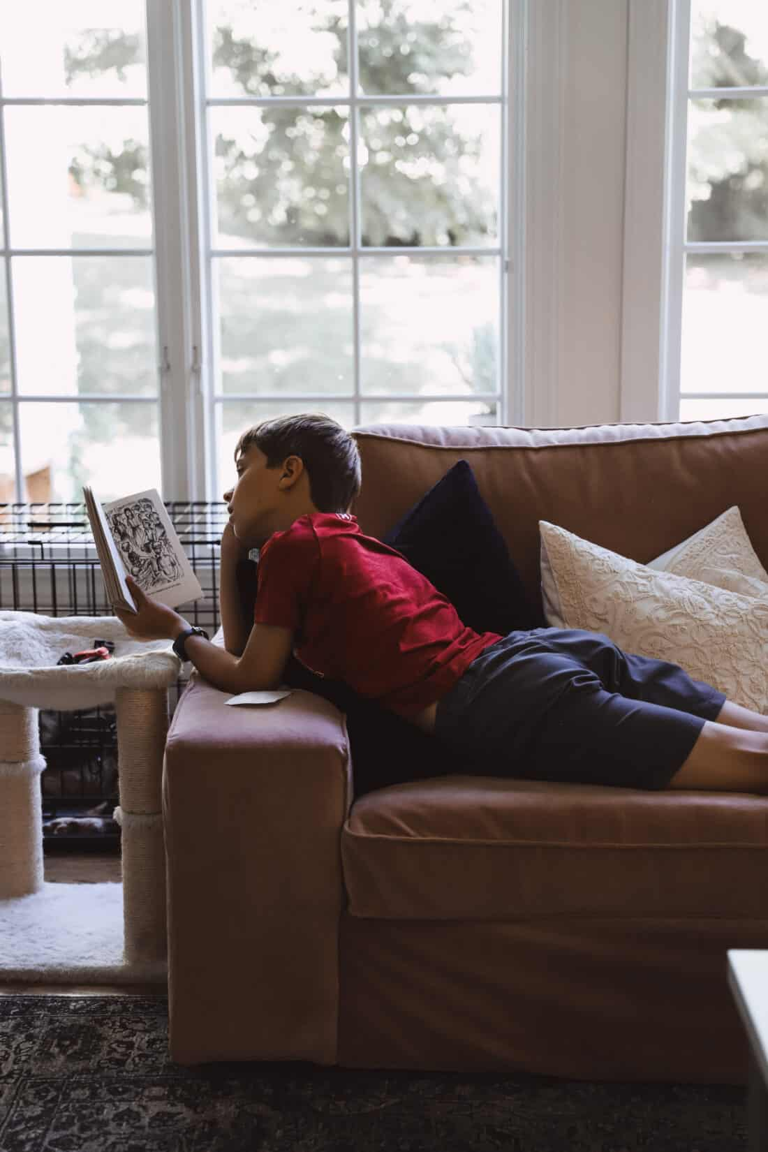 child reading a book on a couch