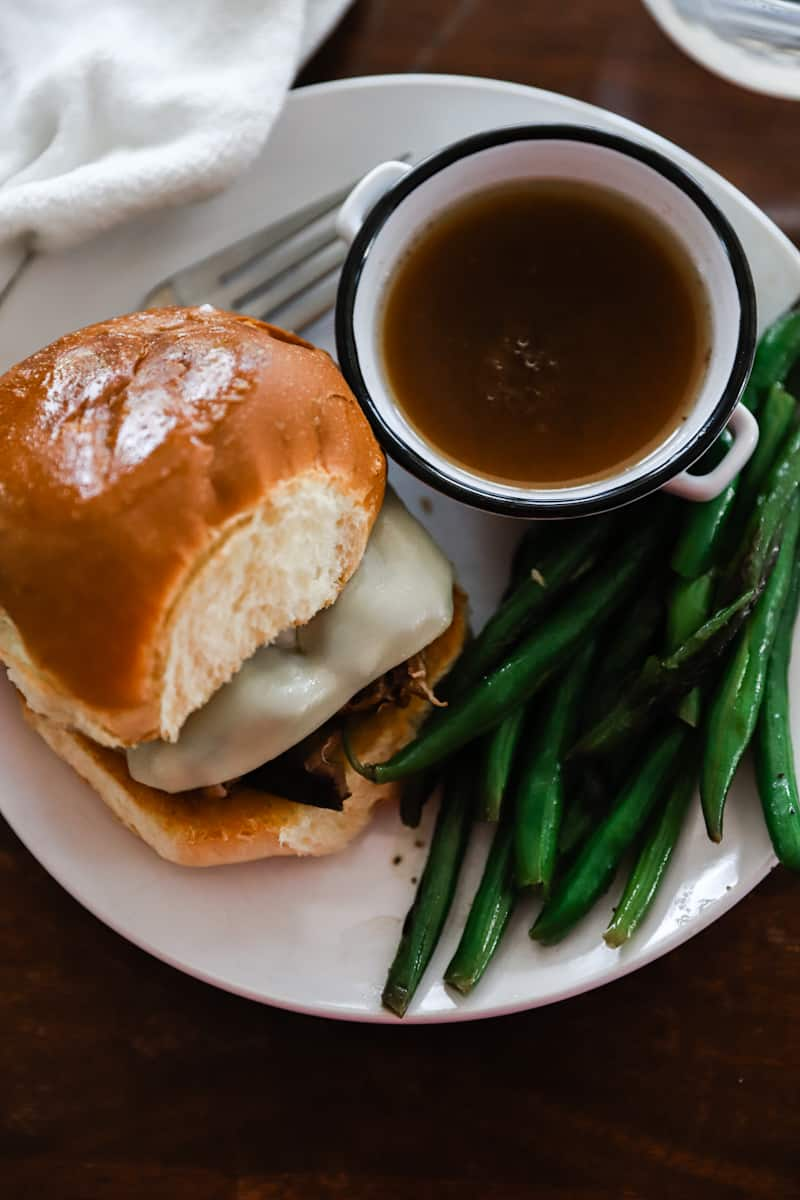 french dip sandwich with green beans on a white plate