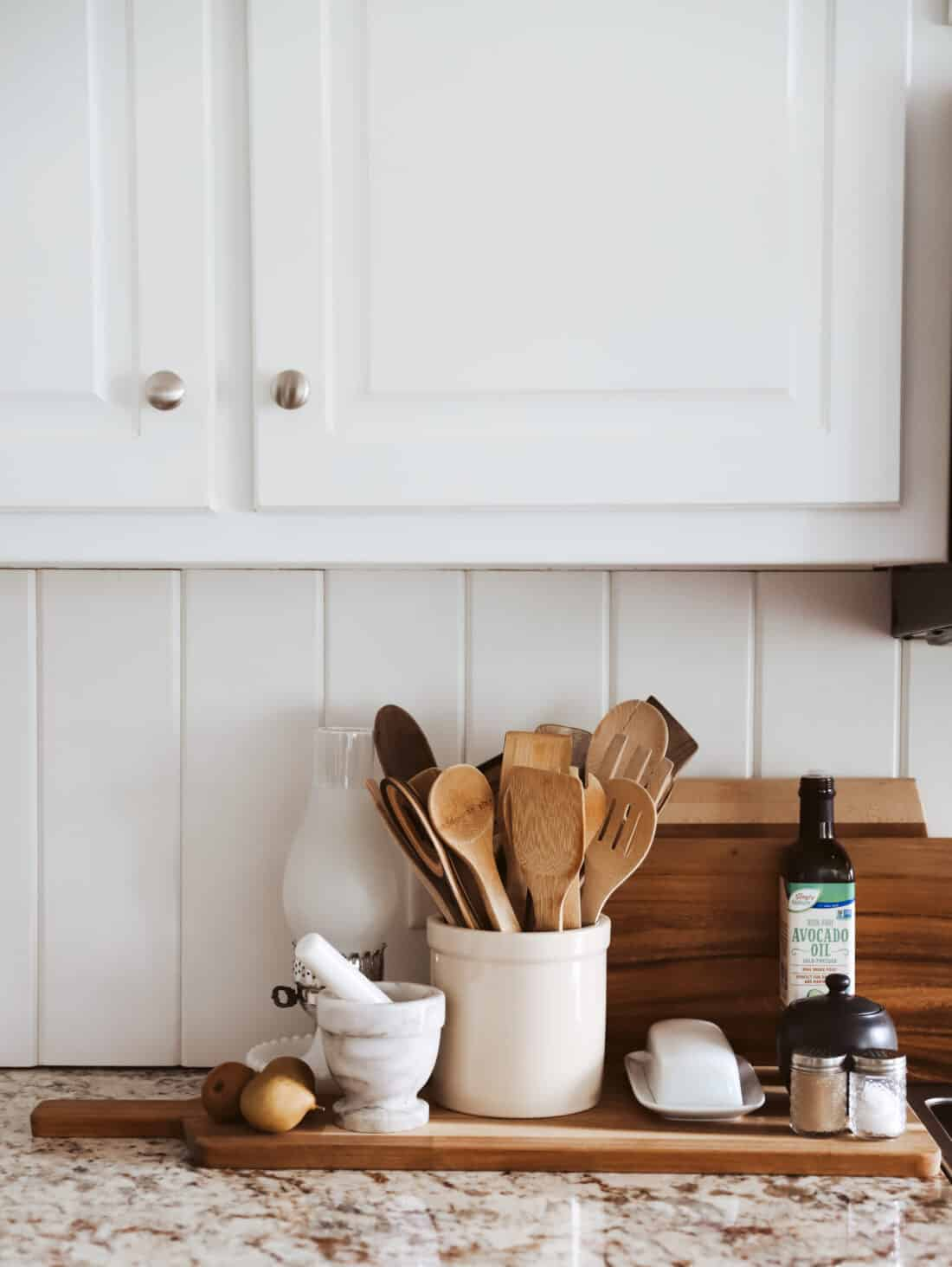 white vertical shiplap in a cottage kitchen with cutting boards leaning on the backsplash